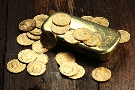 Swiss Vreneli gold coins with gold ingot on wooden background