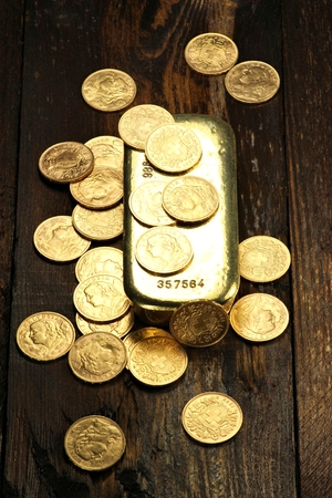 gold ingot: Swiss Vreneli gold coins with gold ingot on wooden background