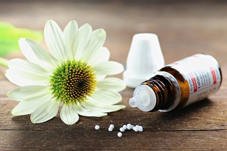 Scattered homeopathic Echinacea pills on wooden background Stock Photo
