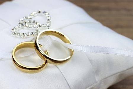 Golden wedding rings on white ringbearer pillow