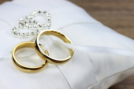 wedding day: Golden wedding rings on white ringbearer pillow