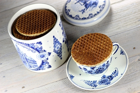 delftware: Traditional Dutch syrup waffles with delftware on wooden background