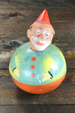 memorabilia: antique roly-poly doll on wooden background