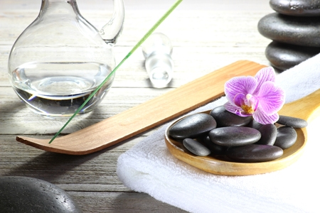 basalt stones for hot stone massage with accessories on wooden background Stock Photo