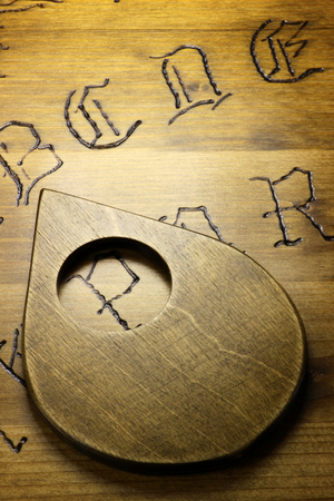 esoterism: planchette on wooden board talking