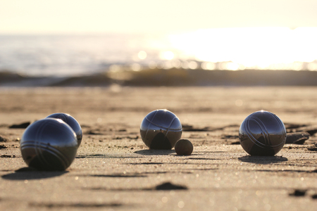 bocce ball: bocce balls on sandy beach Stock Photo