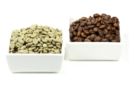 unroasted: roasted and unroasted coffee beans in white bowls isolated on white background