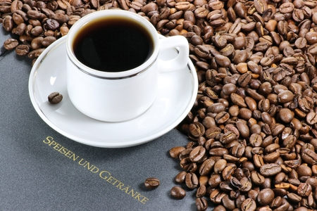 fairtrade: coffee cup with whole coffee beans and German menu Stock Photo