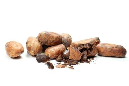 commodities: los granos de cacao tostados aislados en el fondo blanco