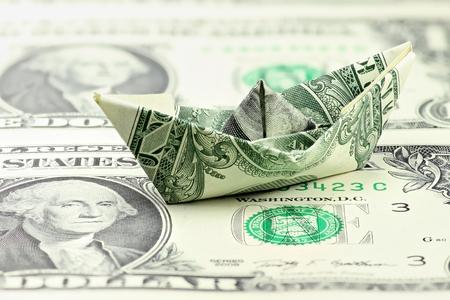 armaments: US Dollar paper boat Stock Photo