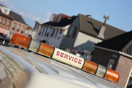 light duty: service vehicle with yellow beacon lights in urban area Stock Photo
