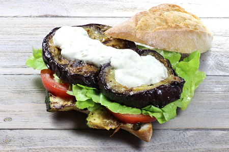 hero sandwich: appetizing roll with grilled vegetables on wooden background