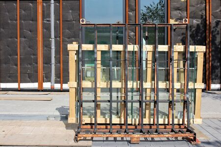 building sector: pallet with window glasses in front of new build