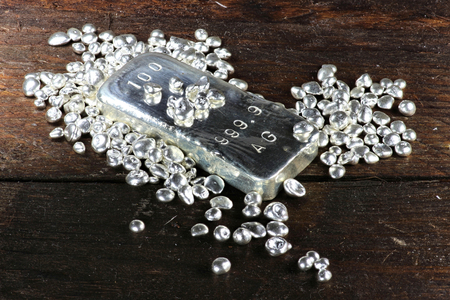 silver bullion: silver ingot and granules on wooden background