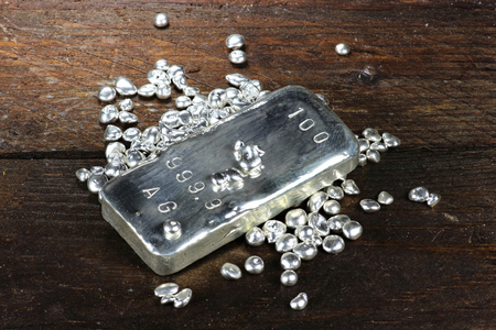 silver bar: silver ingot and granules on wooden background