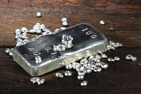 granules: silver ingot and granules on wooden background