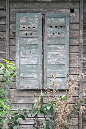 dilapidation: closed highly weathered wooden shutters