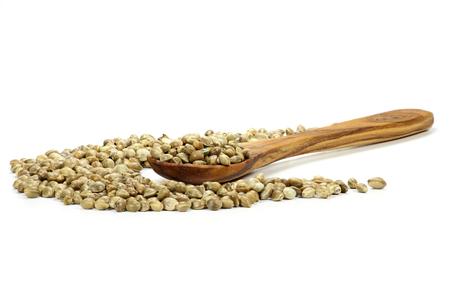 herbolaria: cuchara de madera con semillas de cáñamo aislados en fondo blanco