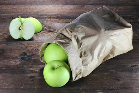 apple paper bag: apples variety Delcorf on wooden background
