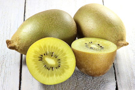 mellowness: golden kiwifruit on wooden background