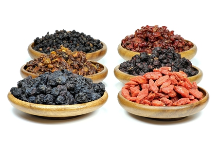 barberries: assortment of dried berries in wooden bowls isolated on white background