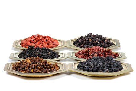 barberries: assortment of dried berries in brass bowls isolated on white background Stock Photo