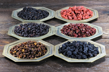 barberries: assortment of dried berries in brass bowls on wooden background