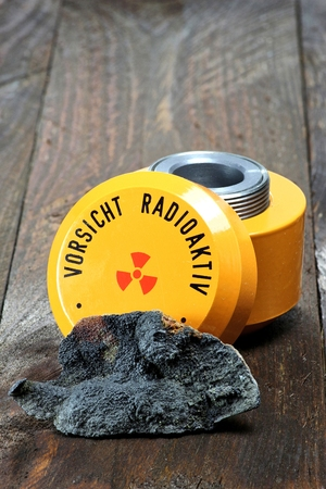 radioactive: uraninite with storage container for radioactive materials