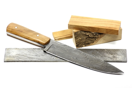 raw materials: handmade damascus kitchen knife with raw materials isolated on white background