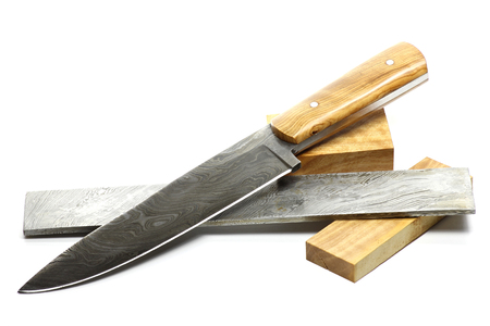 handmade damascus kitchen knife with raw materials isolated on white background