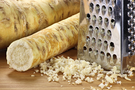 grater: horseradish with grater on wooden background