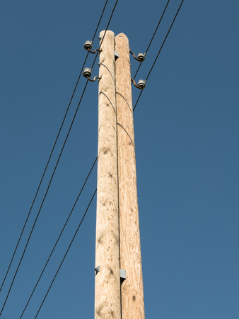 electricity providers: wooden power pole against blue sky