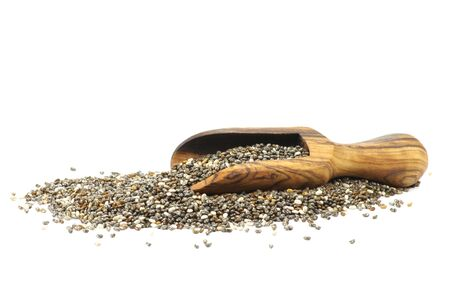 herbolaria: wooden scoop with chia seeds isolated on white background Foto de archivo