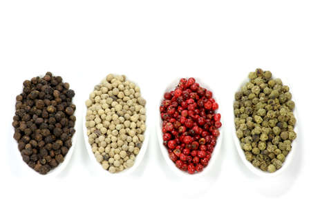 sorted: different colored peppercorns sorted in small ceramic bowls isolated on white background