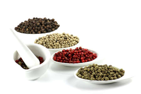 sorted: different colored peppercorns sorted in small bowls with a mortar isolated on white background
