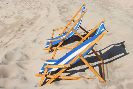folding: folding chairs on sandy beach