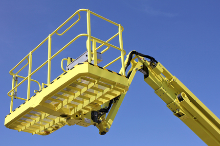 bucket of cherry picker against blue sky