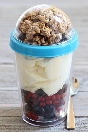 reusable: yogurt with fresh garden berries and cereals in reusable picnic cup on wooden background Stock Photo
