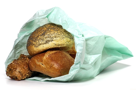 sunday paper: fresh bread rolls in paper bag isolated on white background Stock Photo