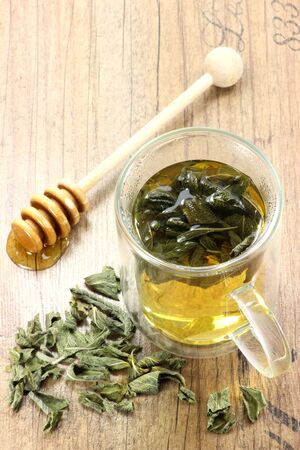 double glass: Sage tea in a double wall glass mug on wooden background