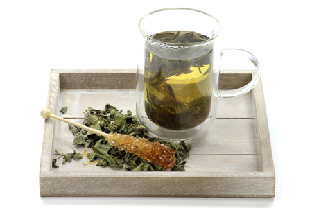 double glass: Sage tea in a double wall glass mug on wooden tray Stock Photo