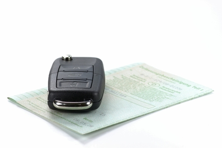 白い背景に分離されたドイツ車両登録証明書と車の鍵 写真素材