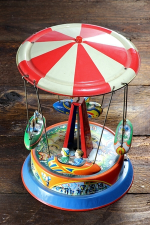 old tin toy carousel on wooden background Stock Photo