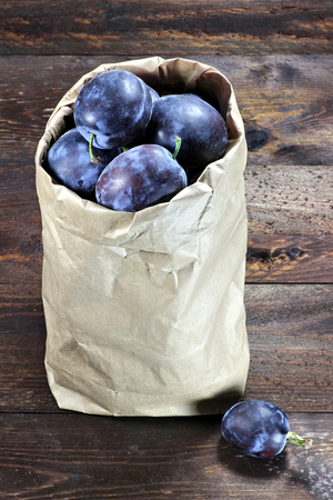 mellowness: damson plums in a paper bag on wooden background