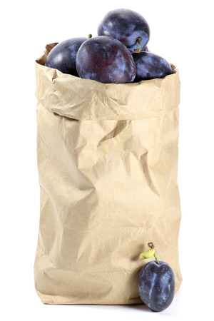 mellowness: damson plums in a paper bag isolated on white background Stock Photo