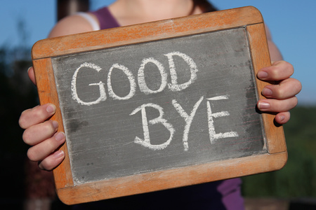 bye: GOOD BYE written with chalk on slate shown by young female Stock Photo