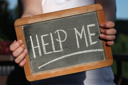suppression: HELP ME written with chalk on slate shown by young female