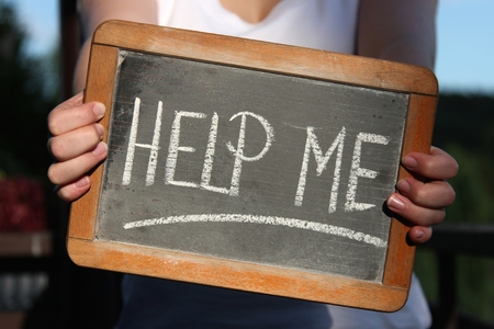 help me: HELP ME written with chalk on slate shown by young female