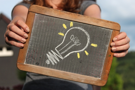 gimmick: bulb sketched with chalk on slate shown by young female