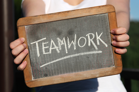 TEAMWORK written with chalk on slate shown by young female